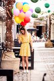 A blonde girl smiles with ballons in hand stock photography