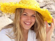 Blonde girl is smiling. Girl with yellow hat is smiling Royalty Free Stock Image