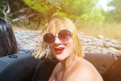 Blonde girl smiling in convertible car. Happy blonde girl sitting and smiling in the back seat of convertible car. Sun effect applied stock photo
