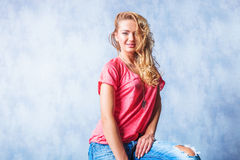 Blonde girl smiling and sitting with rugged jeans and messy hair Royalty Free Stock Photo