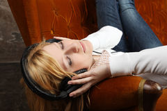 Blonde girl on sofa listening to music with headphones Stock Photo