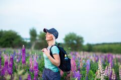 Blonde girl in a sports T-shirt, shorts, baseball cap, breathes water with a backpack, walks on a flower field