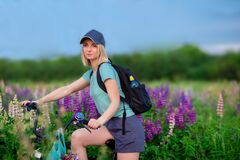 Blonde girl in sportswear, baseball cap, with a backpack on a bicycle walks on a flower field
