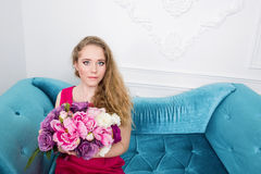 Blonde girl with spring flowers is sitting Royalty Free Stock Images