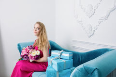 Blonde girl with spring flowers is sitting Stock Photo