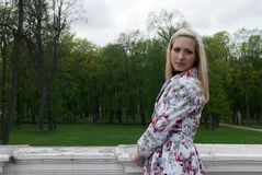 Blonde girl standing against a background of park Stock Image