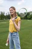 Blonde girl standing with badminton racquet and shuttlecock while looking away Royalty Free Stock Image
