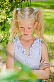 Blonde girl standing in a garden with hands clasped, looking at Royalty Free Stock Photos