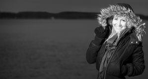 Blonde girl standing at sea b/w. B/w Blonde woman standing smiling at sea in cold weather with open space for text negative fur warm coat black white b/w happy royalty free stock images