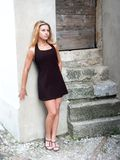 Blonde girl standing by the wall. Blonde girl with long hair in black miniskirt is standing by the wall looking innocently Royalty Free Stock Photo
