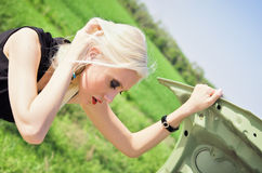 Blonde girl stands by the broken car Royalty Free Stock Photos