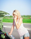 Blonde girl stands near the broken car Stock Photos