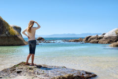 Blonde girl stands on rocky beach Royalty Free Stock Image