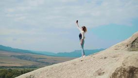 A blonde girl stands on top of a mountain on a background of bright blue sky, she raised her hand with a mobile phone. Transmitting a beautiful view from the stock video