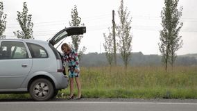 Blonde girl stending near her broken car with open trunk on a country road and read the instruction stock video