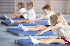 Blonde girl stretching on mat. Blonde girl stretching on a blue mat during physical education classes stock photography