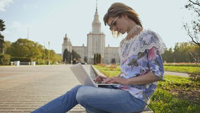 Blonde girl student working with a laptop on a square on the background of Lomonosov Moscow State University. stock video