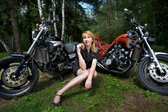 Blonde girl and stylу custom motorcycles Royalty Free Stock Photos