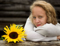Blonde girl and sunflower. Young blonde with a sunflower on the background of a log Stock Photography