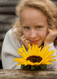 Blonde girl and sunflower. Young blonde with a sunflower on the background of a log Royalty Free Stock Photos
