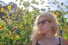 Blonde girl among sunflowers. A beautiful blonde girl in the sunflower field looking to the left Royalty Free Stock Image