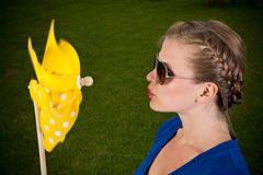 Blonde girl with sunglasses and a pinwheel Royalty Free Stock Images