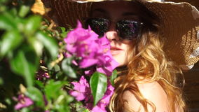 Blonde girl in sunglasses and straw hat posing on camera stock footage
