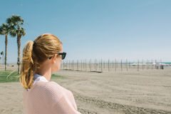 Blonde girl in sunglasses watching the sea, on windy day near th Royalty Free Stock Images