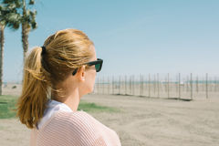 Blonde girl in sunglasses watching the sea, on windy day near th Stock Photography
