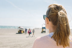 Blonde girl in sunglasses watching the sea, on windy day near th Royalty Free Stock Photos