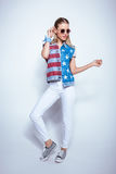 Blonde girl in sunglasses wearing denim vest with us flag and posing in studio Stock Photos
