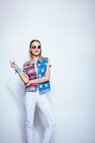 Blonde girl in sunglasses wearing denim vest with us flag and posing in studio Royalty Free Stock Images