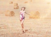 Blonde girl in sunny autumn field Stock Image