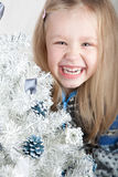 Blonde girl in a sweater laughing next to a white. Christmas tree Stock Image