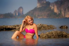 Blonde girl in swimsuit half in sea water Royalty Free Stock Photography