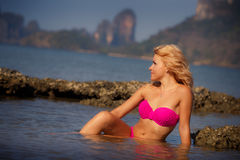 Blonde girl in swimsuit half in sea water Stock Photo
