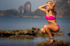 Blonde girl in swimsuit smoothes hair on stone Royalty Free Stock Photo