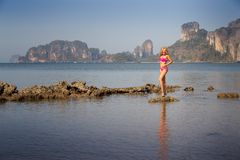Blonde girl in swimsuit stand on sea stones Stock Photo