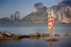 Blonde girl in swimsuit stand on sea stones Stock Images