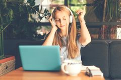 Girl in headphones listening to music. Blonde girl at a table in a cafe with headphones connected to a laptop listening to music and enjoying dancing with stock photos