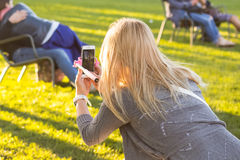 Blonde girl take the photo her friend on her smartphone in the p stock images