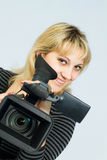 Blonde girl takes on professional video cameras. Stock Photos