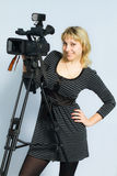 Blonde girl takes on professional video cameras. Stock Images