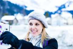 Blonde girl taking a selfie photo on the Swiss Alpine Alps in Switzerland Stock Images