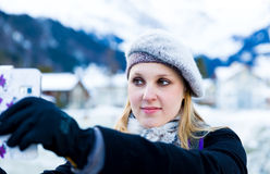 Blonde girl taking a selfie photo on the Swiss Alpine Alps in Switzerland Royalty Free Stock Image