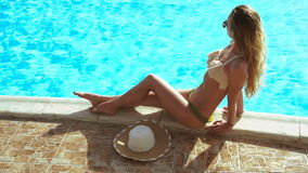 Blonde girl with tan skin sunbathing by the pool stock video