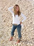 Blonde girl testing water. Girl in white blouse and jeans testing water for coldness royalty free stock photography