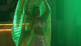 Blonde girl in theatrical costume with wings dances by belly stock footage