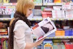 Blonde girl thumbs book in supermarket. Blonde girl wearing scarf thumbs book in supermarket; shallow depth of field stock photos
