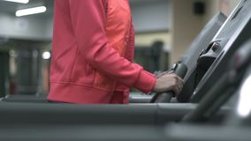 Blonde girl training at the gym on the treadmill stock footage